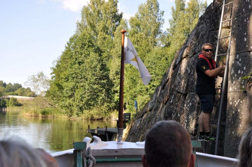 Foto taget ombord på Kinda Kanal i fören. Människor står och tittar ut över vattnet på M/S Kind.