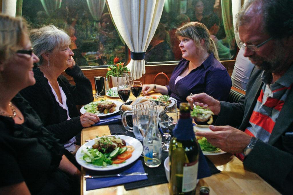 4 personer sitter och äter i M/S Kinds restaurangdel
