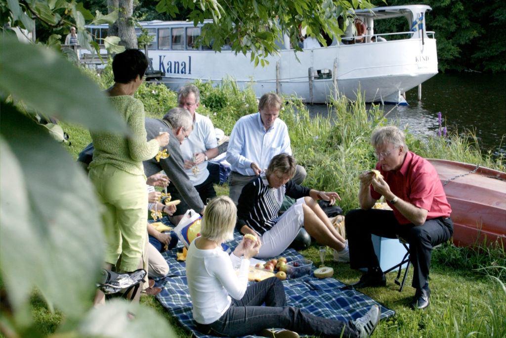 Grupp lunchar i gräset vid sidan av kanalen och M/S Kind