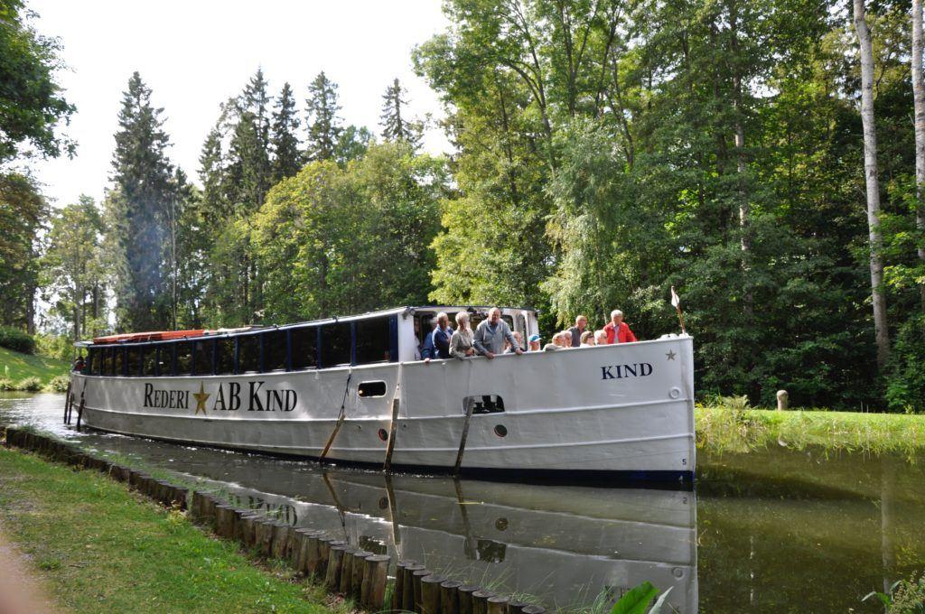 M/S Kind glider fram på kanalen i ett somrigt landskap